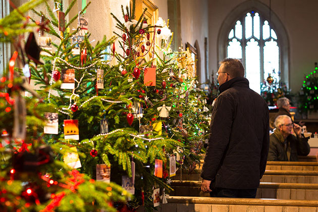 Image of a man looking at the Christmas trees in church