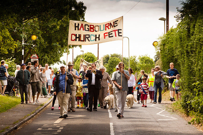 Image of village folk walking with banner to the fete