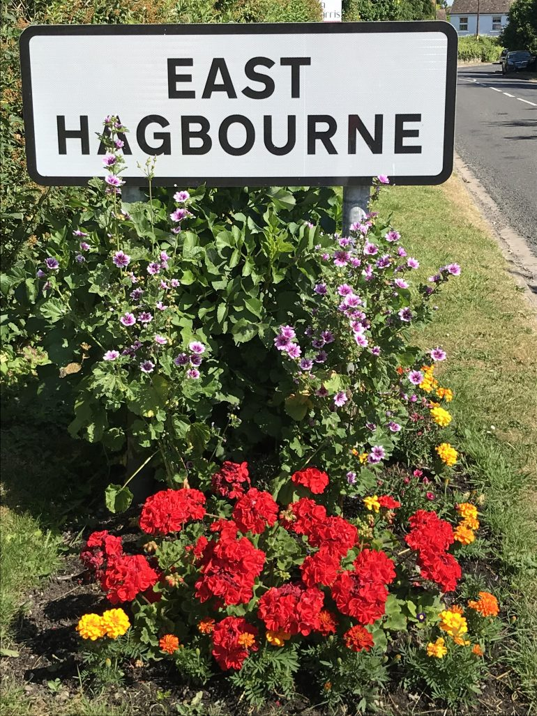 Image of the village sign post and flowers