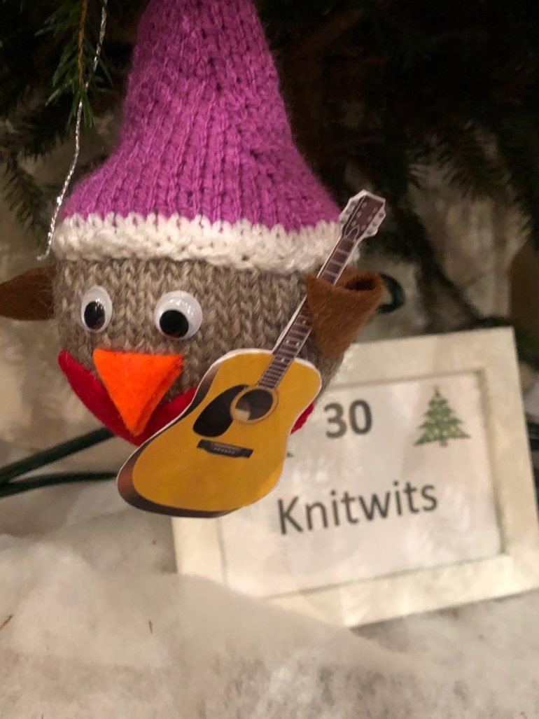 Image of a small knitted bird holding a paper guitar